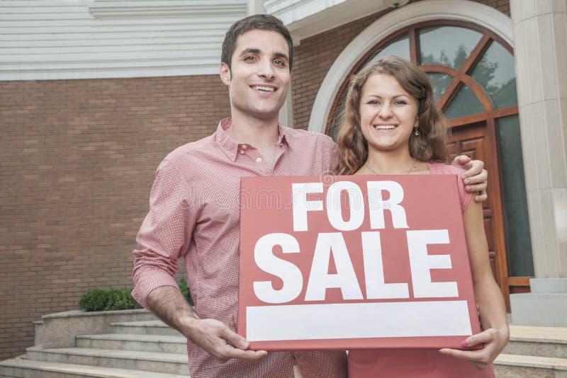 举行a待售标志的微笑的年轻夫妇 免版税库存照片