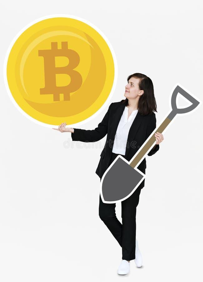 举行bitcoin cryptocurrency和开采概念象的女实业家 免版税库存图片