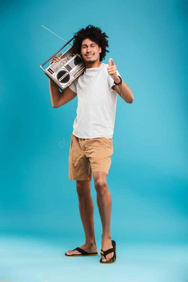 举行boombox指向的愉快的年轻非洲卷曲人 图库摄影