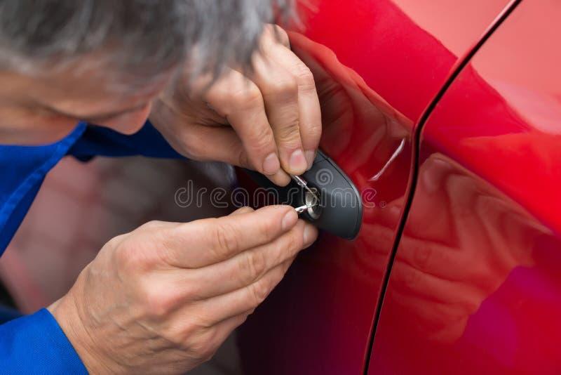 举行Lockpicker的手打开车门 库存图片