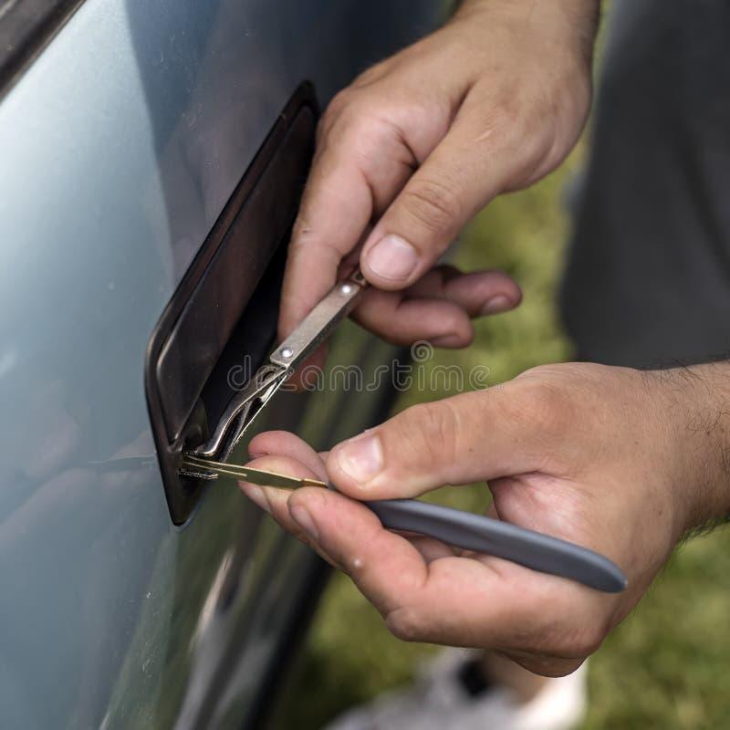 举行Lockpicker的男性技工打开车门 免版税库存照片
