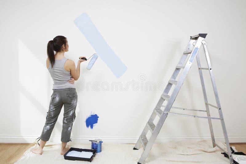 举行Paintroller的妇女,当分析在墙壁上时的油漆 图库摄影