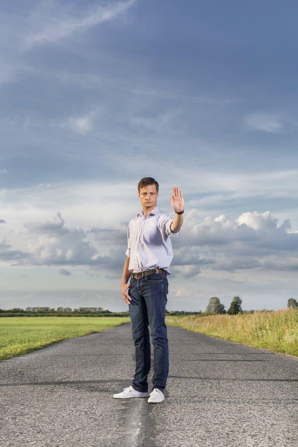 举起手的全长严肃的年轻人停止在乡下公路 免版税库存图片