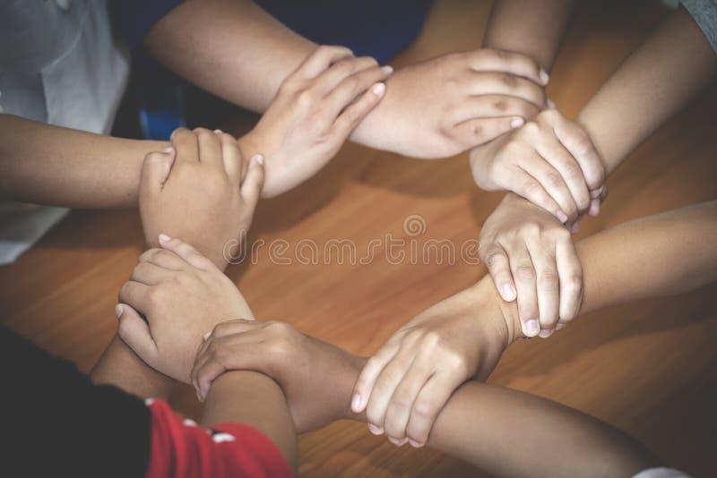 举起手的年轻队为新的起动在创造性的办公室,队配合统一性合作共同工作和配合 库存照片