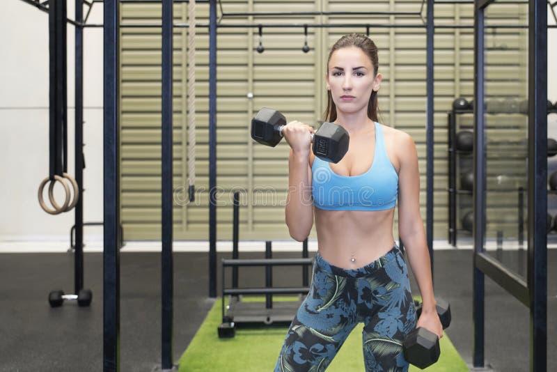 举重的哑铃的活跃白种人女性,制定出她的胳膊在健身房 库存图片