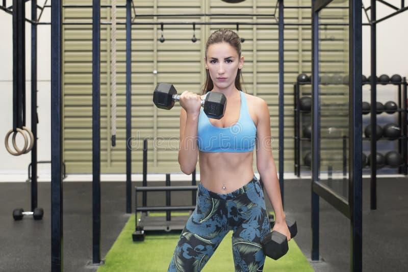 举重的哑铃的活跃白种人女性,制定出她的胳膊在健身房 免版税库存照片
