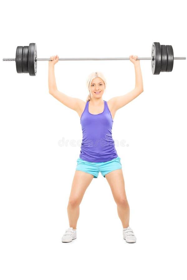 举重的杠铃的白肤金发的女运动员 库存照片