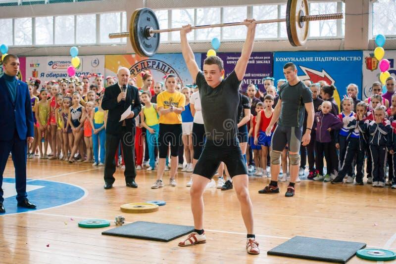 举重运动员表示表现冠军的在啦啦队欢呼,年轻人举重的杠铃,杠铃重量- 80 免版税库存照片