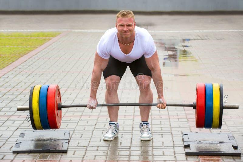 举重运动员运动员提高在街道上的标准 库存照片
