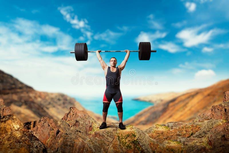 举重运动员采取在山上面的重量  库存照片