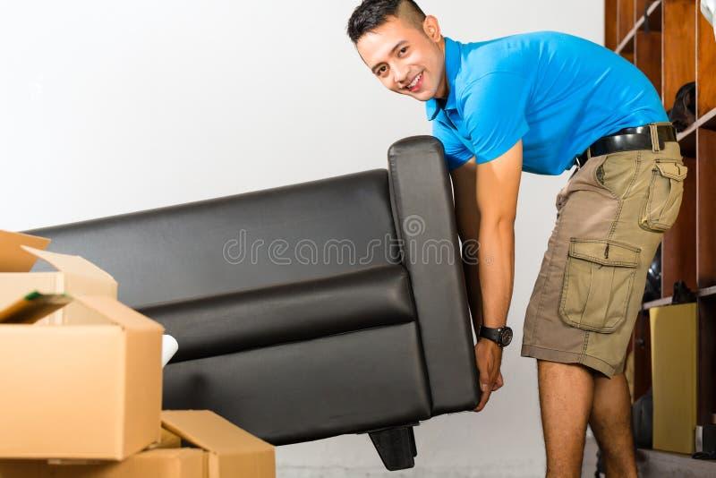 举长沙发的年轻亚裔人 免版税库存图片