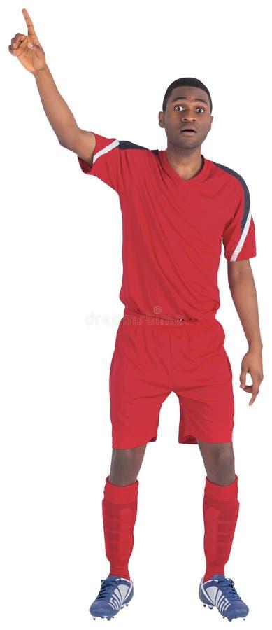 举他的手的红色的足球运动员 图库摄影