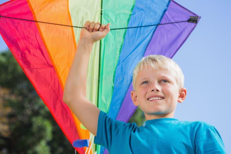 举他的有一只风筝的孩子胳膊在它 免版税库存图片