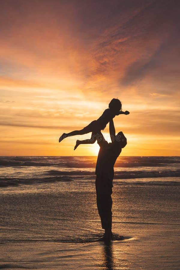 举他的海滩的女儿的父亲 免版税库存照片