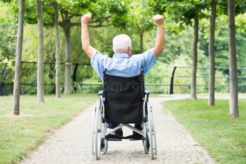 举他的胳膊的轮椅的老人 免版税库存图片