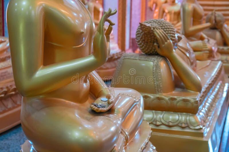 义务捐赠硬币在蜡镀金面形象修士的棕榈说谎在佛教寺庙的 提供的概念,祷告,希望,尊敬 库存照片