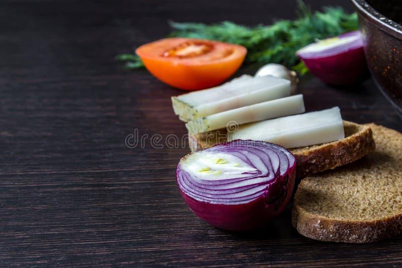 乌克兰全国食物是猪油salo用面包用在蕃茄的背景的红洋葱用在木桌上的大蒜 库存图片