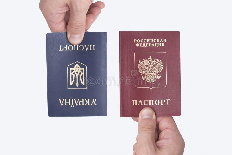 乌克兰和俄国国际护照在人` s手上 库存照片