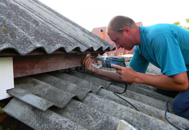 乌克兰基辅–2019年9月27日:安装塑料屋顶檐槽支架的承包商 塑料屋顶嘎吱嘎吱,雨嘎吱 免版税库存图片