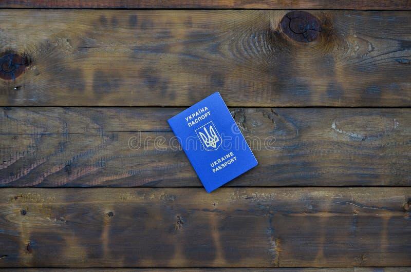 乌克兰外国护照的照片,说谎黑暗的木表面上 介绍Ukrainia的免签证旅行的概念 免版税库存图片