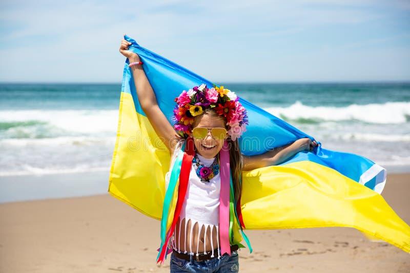 乌克兰女孩举着振翼在天空蔚蓝背景的乌克兰的蓝色和黄旗 免版税图库摄影