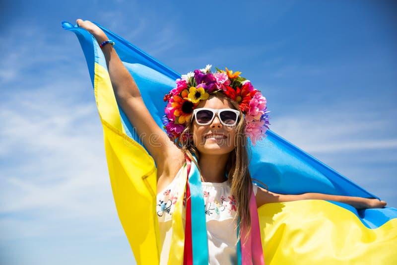 乌克兰女孩举着振翼在天空蔚蓝背景的乌克兰的蓝色和黄旗 免版税库存照片
