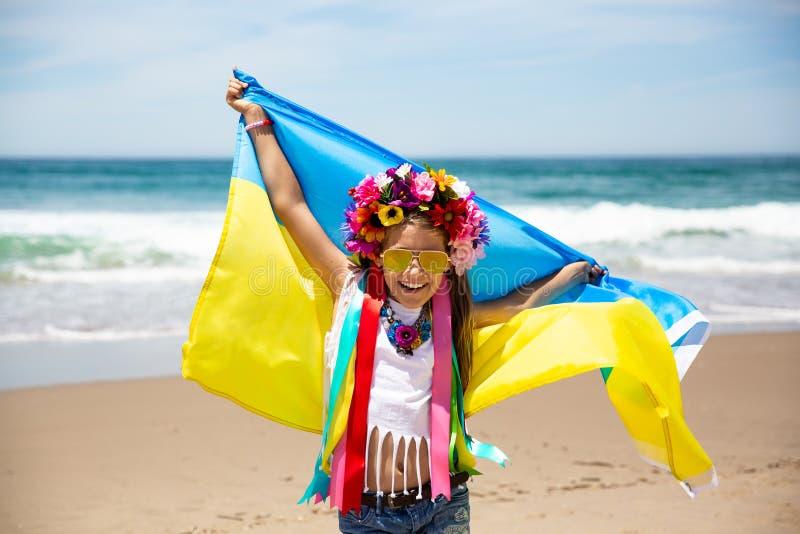 乌克兰女孩举着振翼在天空蔚蓝背景的乌克兰的蓝色和黄旗 库存图片
