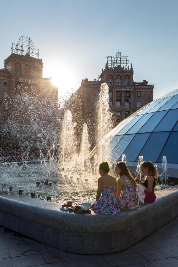 乌克兰女孩坐喷泉在独立广场的一热的天在基辅,乌克兰 图库摄影
