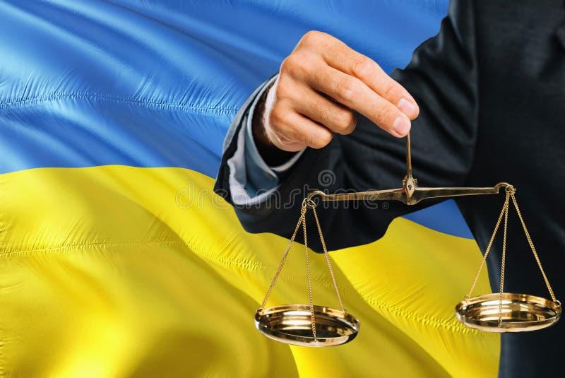 乌克兰法官拿着正义金黄标度有乌克兰挥动的旗子背景 平等题材和法律概念 免版税库存图片