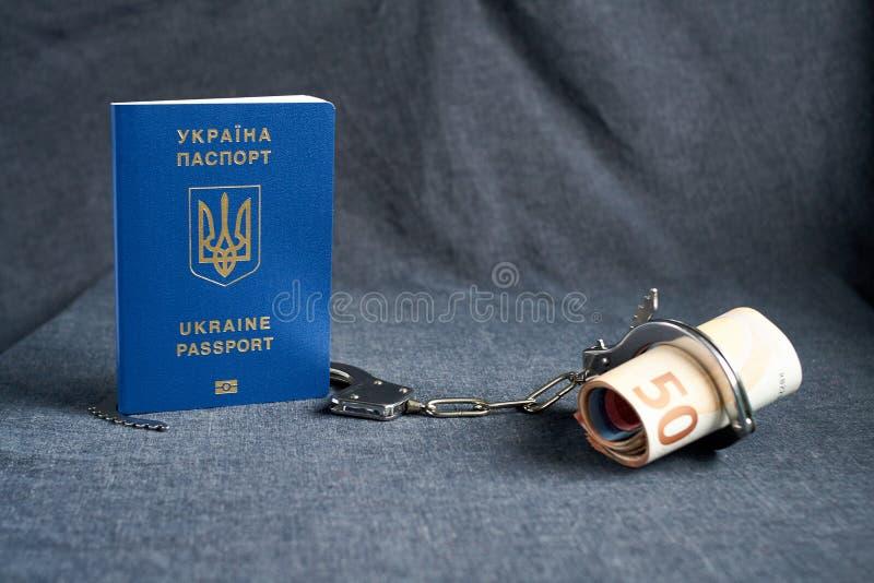 乌克兰生物统计的护照和手铐在桌上 库存照片