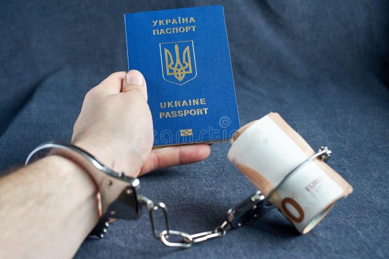 乌克兰生物统计的护照和手铐在桌上 免版税库存图片
