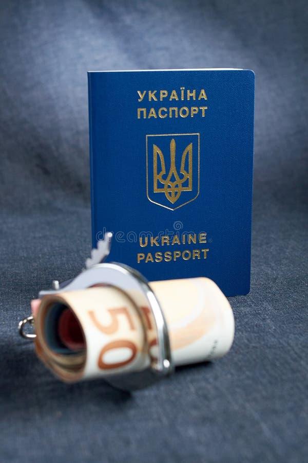 乌克兰生物统计的护照和手铐在桌上 免版税库存照片