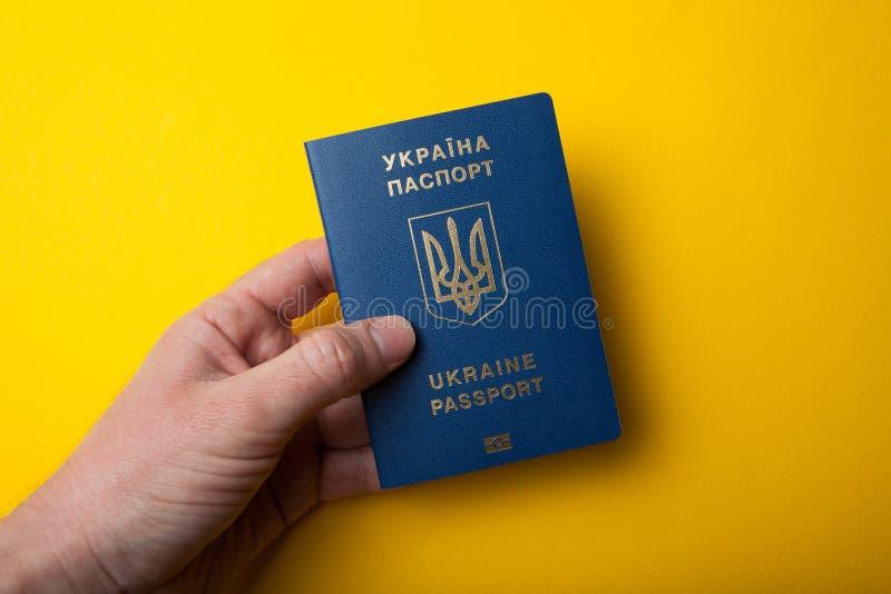 乌克兰生物统计的护照id在手中在黄色背景 免版税库存照片