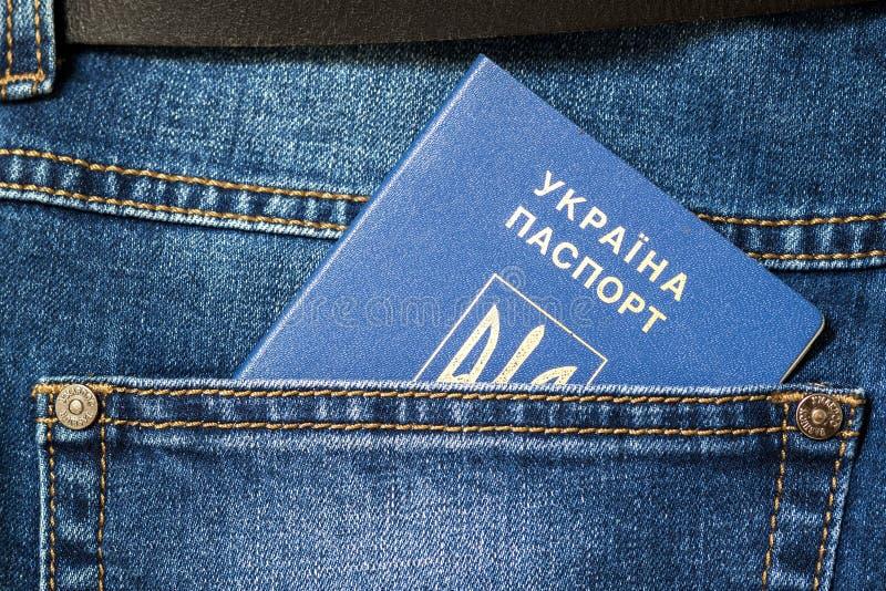 乌克兰的护照蓝色牛仔裤的一个口袋的关闭  库存图片
