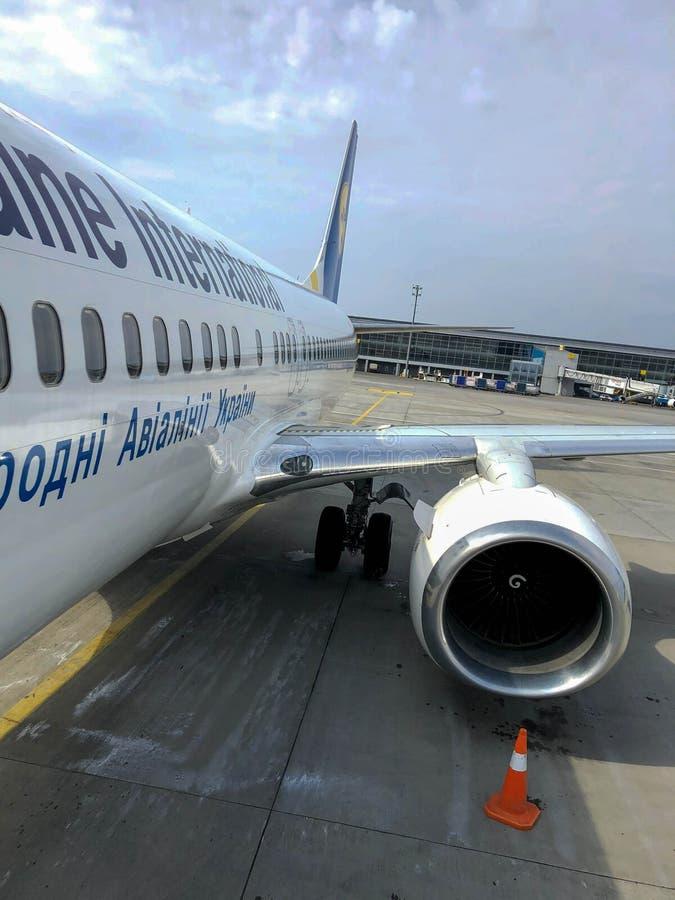 乌克兰航空公司美好的快速的白色喷气机与引擎和翼的在跑道在机场 乌克兰,基辅,2019年4月17日 库存图片