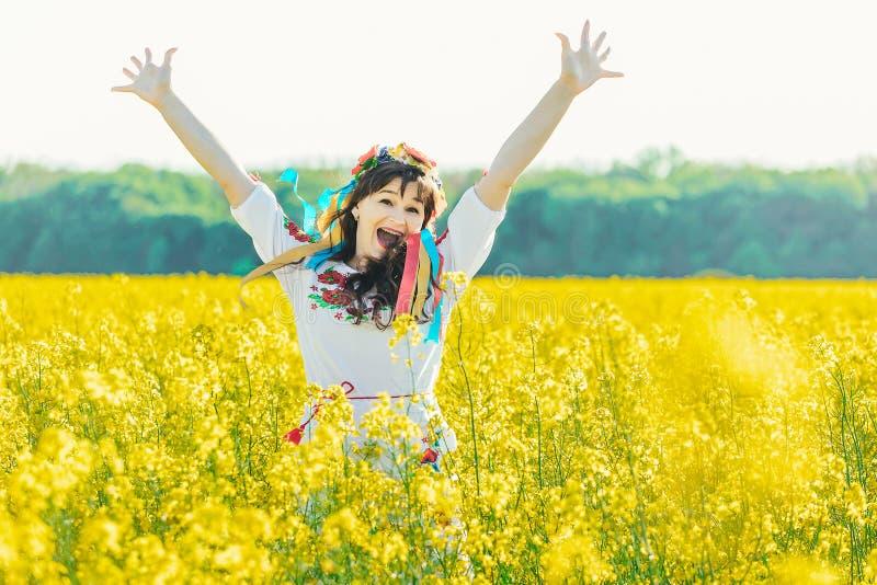 乌克兰语的美丽的少妇绣了在黄色强奸花的领域的身分 库存图片