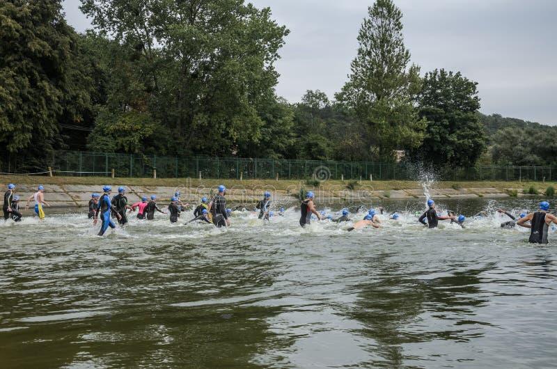 乌克兰,利沃夫州- 2018年9月:保温潜水服的运动员起初跑入游泳的水在三项全能竞争中 库存图片