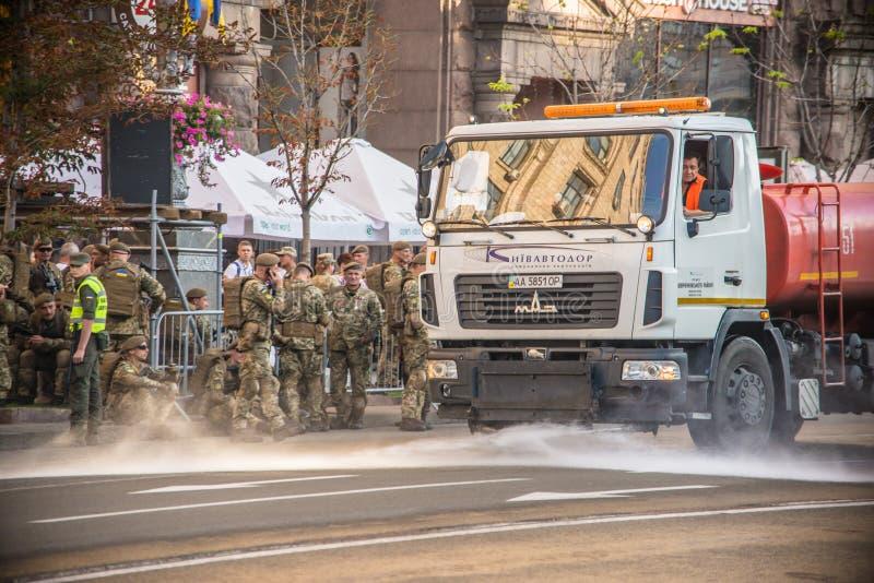乌克兰,基辅,2018年8月24日 白色浇灌的机器和橘黄色洗涤基辅街道  库存图片
