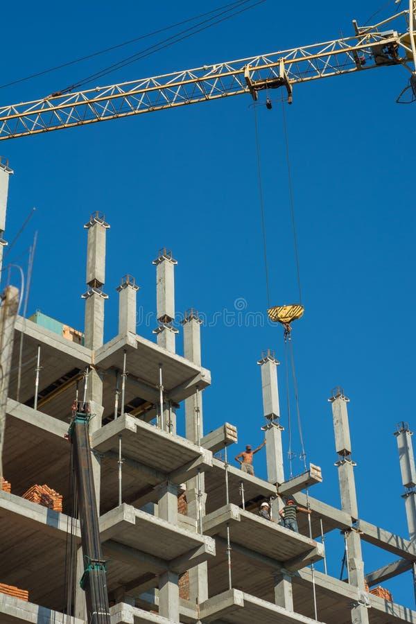 乌克兰,涅任- 2016年7月14日:建造者和大厦塔吊在建造场所 库存图片