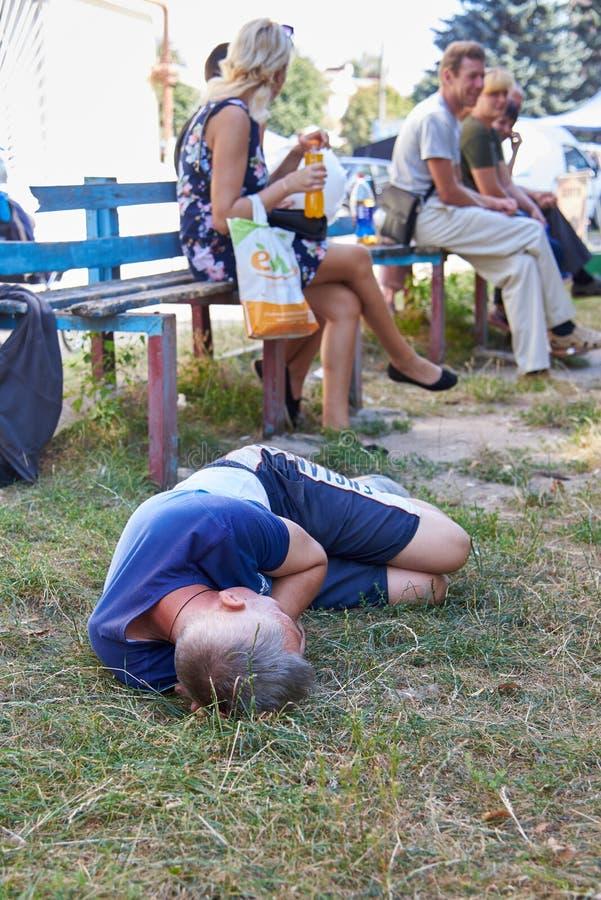 乌克兰,绍斯特卡 — 2019年9月3日:醉汉躺在地上,酗酒和错误生活方式的主题 免版税库存图片