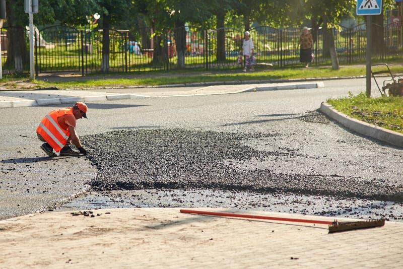 乌克兰,绍斯特卡- 2019年6月14日:工作者热的沥青为放置一条新的路的本地建筑做准备 免版税库存图片