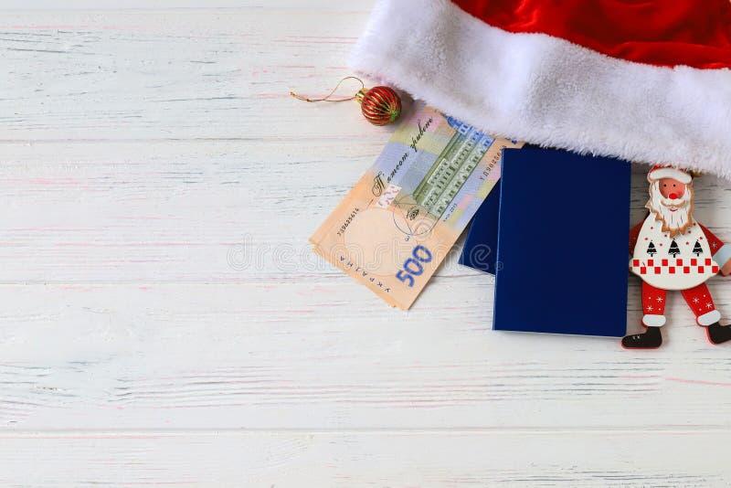 乌克兰hryvna,钞票500 hryvnia,与红色圣诞老人项目帽子和蓝色护照在老光,木背景 免版税图库摄影