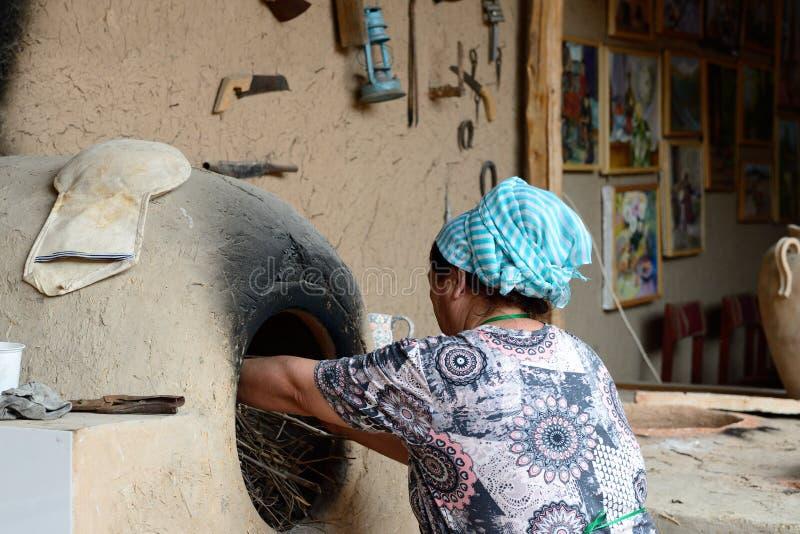 乌兹别克人妇女和传统tandyr烤箱,Rishtan,费尔干纳盆地,乌兹别克斯坦 库存照片