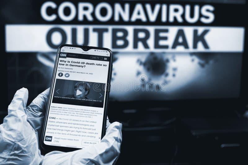 乌兹别克斯坦塔什干 — 2020年3月26日:德国医生在智能手机上查看COVID-19情况 图库摄影