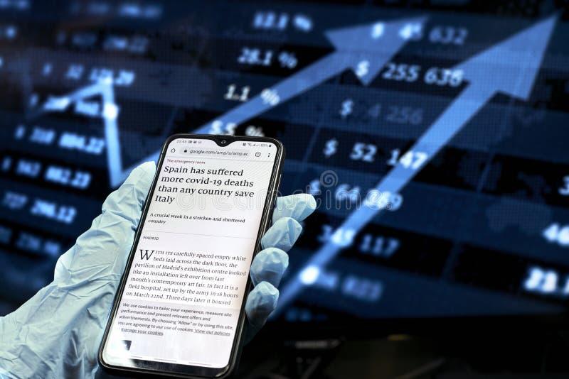 乌兹别克斯坦塔什干 — 2020年3月26日:COVID-19自检 在冠状病毒肆虐期间,商人在智能手机上查看新闻 免版税库存图片