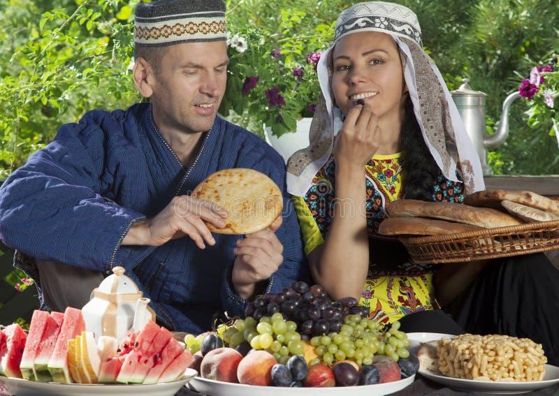 乌兹别克斯坦夫妇食用与平的蛋糕的早餐 免版税库存图片