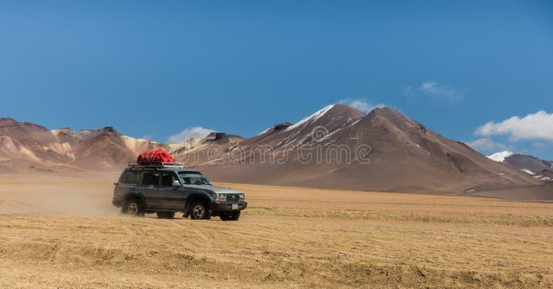 乌尤尼盐沼,玻利维亚,吉普在有火山的沙漠在背景中 图库摄影