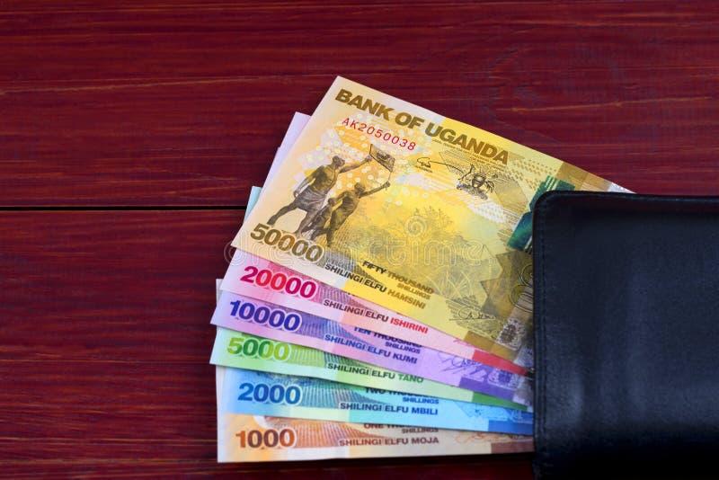 乌干达先令在黑钱包里 库存图片