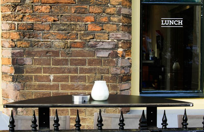 乌得勒支,荷兰- 10月20 2018年:在被隔绝的空的黑桌上的看法与烟灰缸有窗口和砖的餐馆外 免版税库存照片