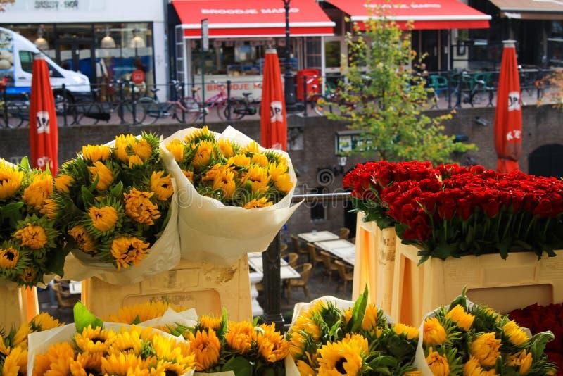 乌得勒支,荷兰- 10月20 2018年:在黄色向日葵和红色郁金香花束的看法在水运河附近在花市场上 免版税图库摄影